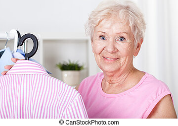Elderly woman hanging shirt on hanger