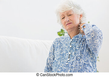 Elderly woman having a neck pain in the living room