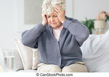 Elderly woman having migraine headache