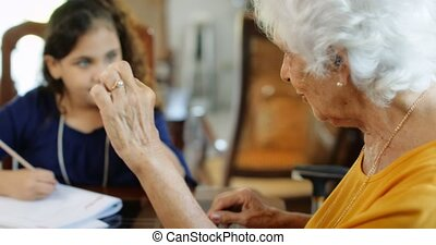 Elderly Woman Helping Little Girl Doing School Homework