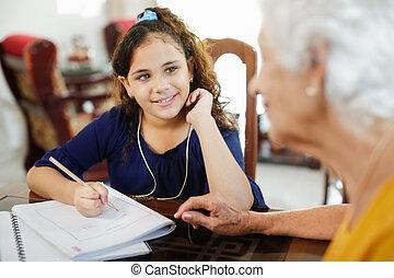 Elderly Woman Helping Little Girl Doing School Homework