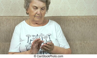 Elderly woman holding a mobile phone at home