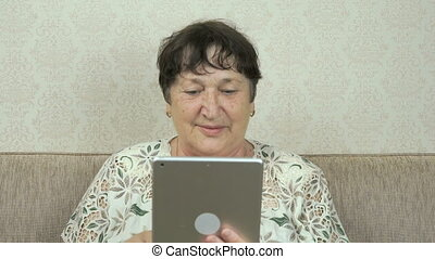 Elderly woman holding a silver digital tablet