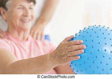 Elderly woman holding blue ball