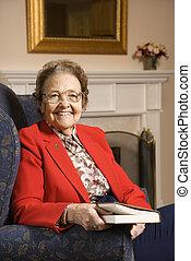 Elderly woman holding book.