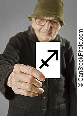 Elderly woman holding card with printed horoscope Sagittarius sign.