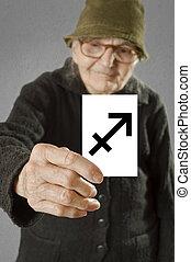 Elderly woman holding card with printed horoscope Sagittarius sign.
