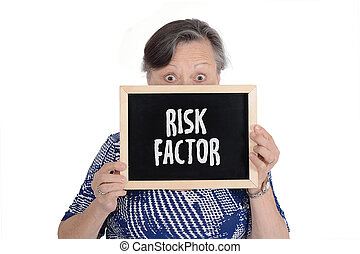 """Elderly woman holding chalkboard with text """"risk factor"""""""