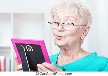 Elderly woman holding frame