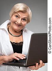 Elderly woman holding the laptop