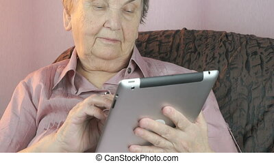 Elderly woman holding the silver tablet computer