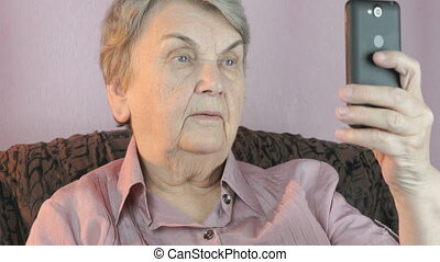 Elderly woman holding the smartphone indoors