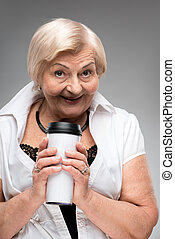 Elderly woman holding thermos cup - Taking some time for...