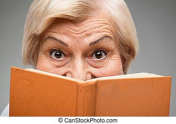 Elderly woman holding yellow book - I love reading. Closeup...