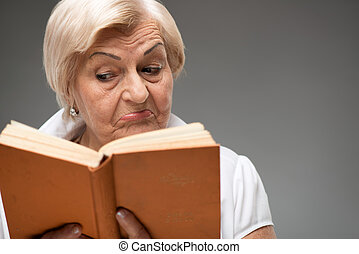 Elderly woman holding yellow book - Fiction book. Closeup of...