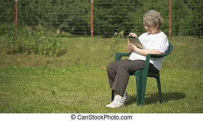 Elderly woman holds a computer tablet outdoors