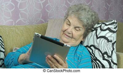 Elderly woman holds a digital tablet indoors