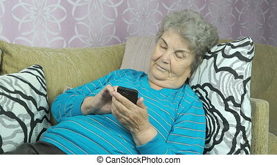 Elderly woman holds a mobile phone indoors