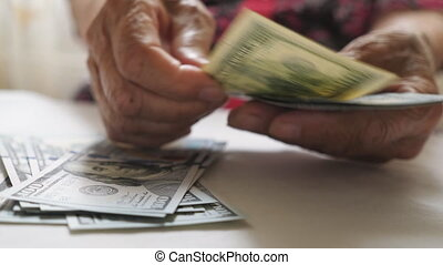 Elderly woman holds cash in arms and counts foreign currency over the table. Close up hands of old grandmother puts one hundred dollar banknotes on the desk. Money concept. Low view Slow motion.
