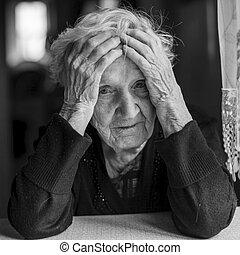Elderly woman holds hands a head
