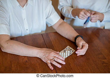 Elderly woman holds pills and ampoule. Close-up of pensioner's hands with drugs. Young woman unpacks the syringe. Daughter is going to give an injection to an elderly mother