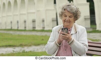 Elderly woman holds silver mobile phone outdoors - Elderly...