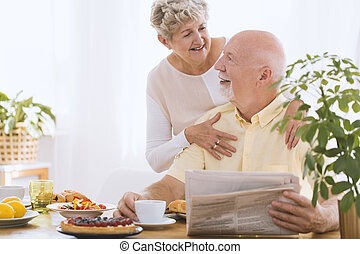 Elderly woman hugging smiling husband
