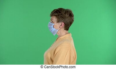 Elderly woman in a medical mask on her face to protecting yourself from coronavirus pandemic isolated over green background. Profile view