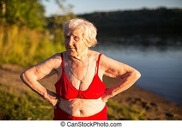 Elderly woman in a swimsuit is on the river bank.
