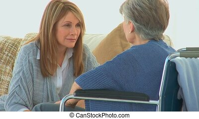 Elderly woman in a wheelchair speaking to her friend in the living room