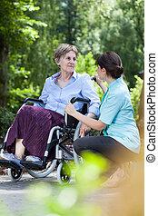 Elderly woman in a wheelchair with a nurse