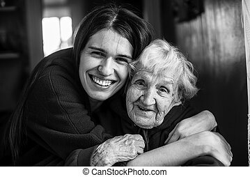 Elderly woman in an embrace with his adult daughter.