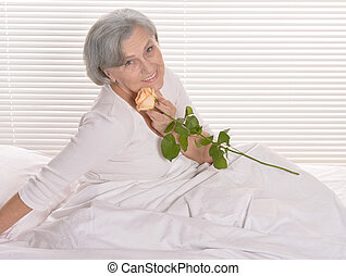 Elderly woman in bed with rose
