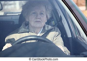Elderly woman in car through windshield