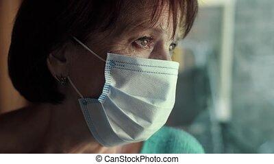 Elderly woman in face mask behind window