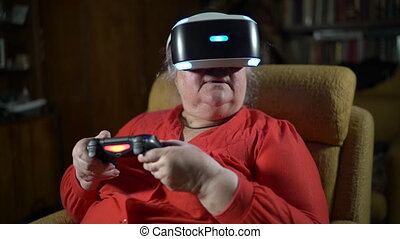 Elderly woman in front of TV screen uses VR headset and wireless gaming controller