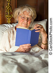 Elderly woman in her nightgown reading in bed
