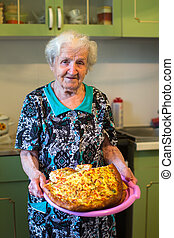 Elderly woman in the kitchen with a pie in his hands.