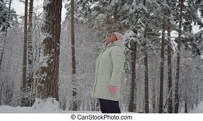 Elderly woman in warm clothing standing in the middle of snow-covered forest and admiring the beautiful scenery. Useful walking outdoors. Bright winter day.