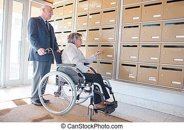 elderly woman in wheelchair checking mail box