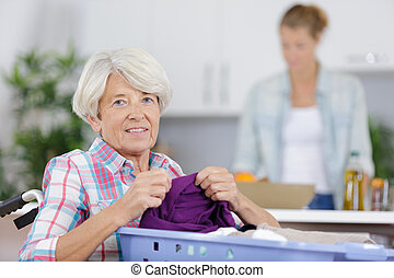elderly woman in wheelchair holding a laundry basket