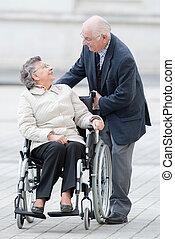 elderly woman in wheelchair turning around to talk to husband