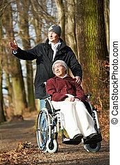 elderly woman in wheelchair walking with son