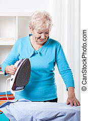 Elderly woman ironing