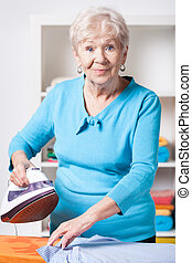 Elderly woman ironing shirt