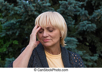 Elderly woman is having a headache and touching her head ...