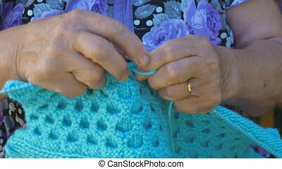 Elderly woman knitting sitting on the street outside his home.