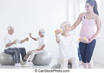 Elderly woman lifting with dumbbels