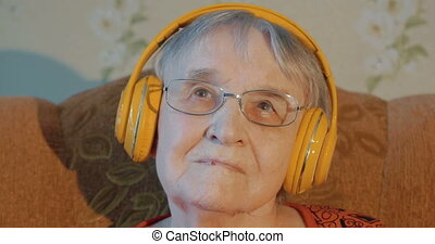 Elderly woman listening to music in headphones