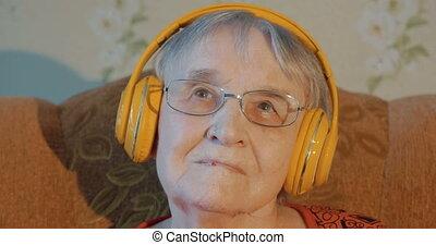 Elderly woman listening to music in headphones